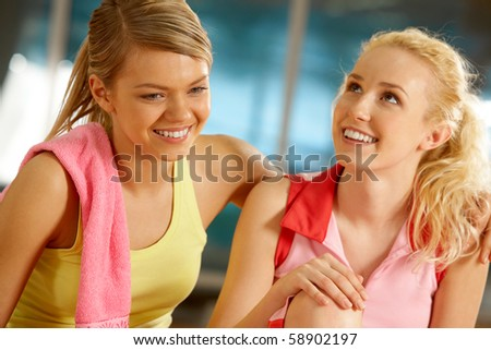 Portrait of two pretty girls during workout in gym - stock photo
