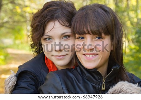 Portrait of two pretty girls in autumn park - stock photo