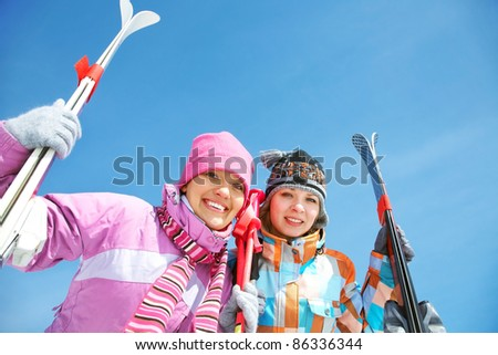 Portrait of two pretty girls with skis - stock photo