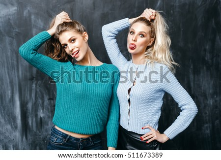 portrait of two pretty hipster sisters wearing colorful knit sweaters . Girls smile, have fun against black wall.