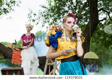 Portrait of two pretty romantic women on a picnic in a fairy forest. Outdoors. - stock photo