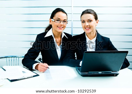 Portrait of two pretty white-collar workers sitting at the table with a laptop, papers and a pen on it - stock photo