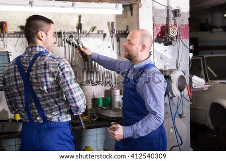 Portrait of two professional car mechanics working together at garage - stock photo