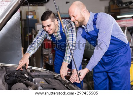 Portrait of two professional car mechanics working together at garage and smiling  - stock photo