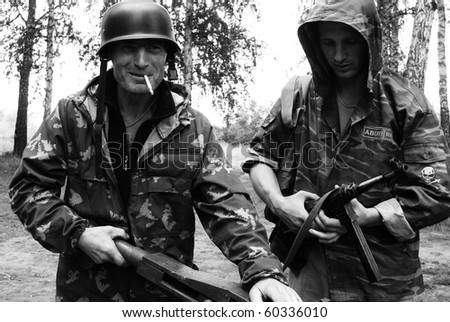 Portrait of two resting smoking soldiers on war ready to fight