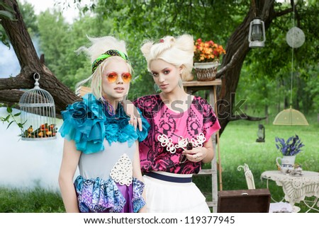 Portrait of two romantic women on a picnic in a fairy forest. Outdoors. - stock photo