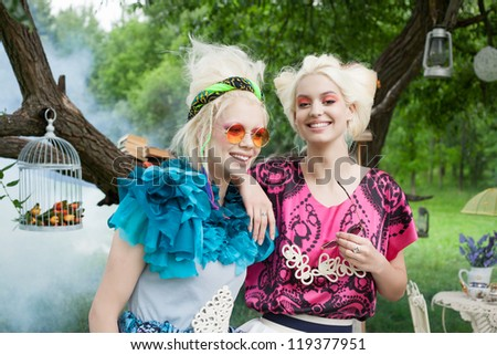 Portrait of two romantic women smiling on a picnic in a fairy forest. Outdoors. - stock photo