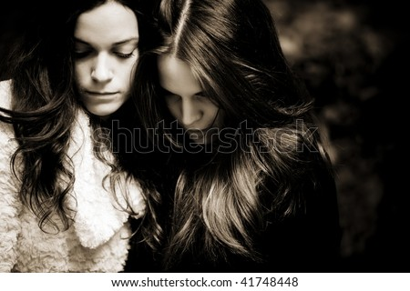 Portrait of two sad girls, dark sepia toned. - stock photo
