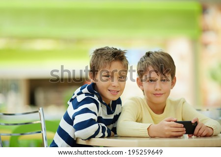 Portrait of two schoolboys sitting at table - stock photo