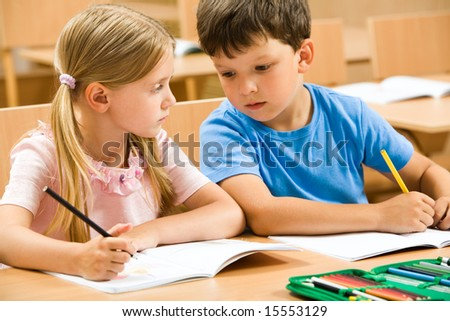 Portrait of two schoolchildren sitting by one desk during drawing lesson while boy looking at his mateâ??s copybook and girl watching at him - stock photo