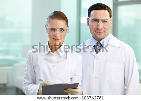 Portrait of two scientists looking at camera and smiling - stock photo