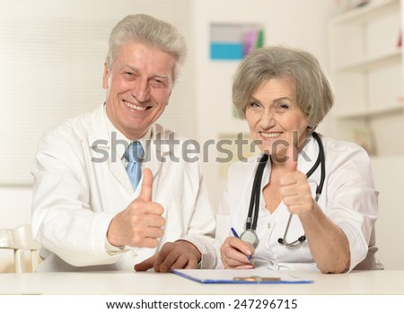 Portrait of two senior doctors show thumbs up - stock photo