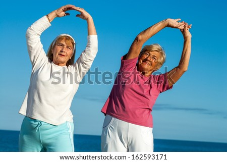 Portrait of two senior fitness ladies stretching arms outdoors. - stock photo