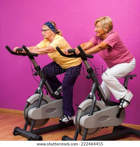 Portrait of two senior girl friends at spinning session in health club.