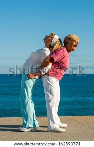 Portrait of two senior ladies helping each other with stretching exercise outdoors. - stock photo