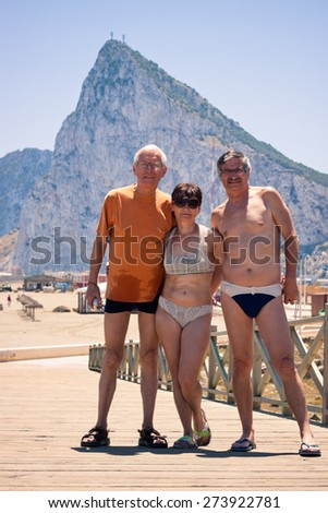 Portrait of two senior men and middle aged woman posing for a photo on the beach with Gibraltar rock on the background.