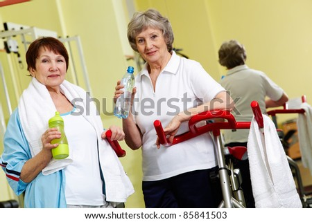 Portrait of two senior women in gym looking at camera - stock photo