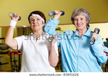 Portrait of two senior women lifting dumbbells - stock photo
