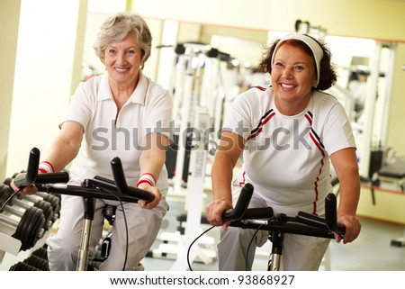 Portrait of two senior women on simulators in fitness club - stock photo