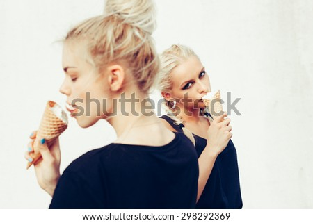 Portrait of two sensuality young beautiful girls eating sweet ice-cream. Outdoors lifestyle - stock photo