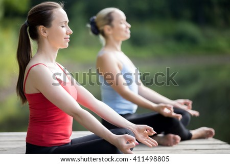 Portrait of two serene smiling beautiful sporty fit young women working out outdoors in park on summer day, Sitting in Easy (Pleasant Posture), Sukhasana, meditating with closed eyes, breathing - stock photo