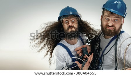 Portrait of two silly antagionistic engineers - stock photo