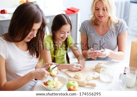 Portrait of two sisters and their mother cooking pastry in the kitchen - stock photo