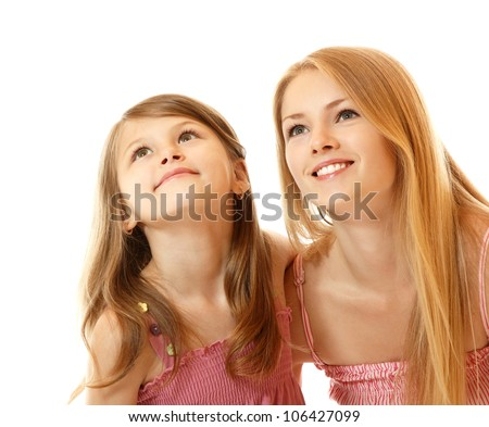 portrait of two sisters happy smiling (child and teen) looking up to corner, isolated on white background - stock photo