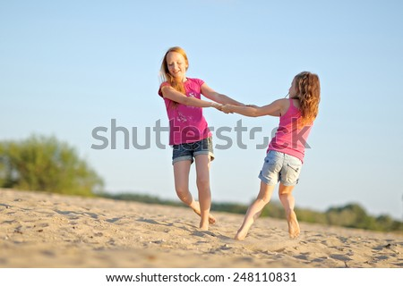 portrait of two sisters walking on the beach - stock photo