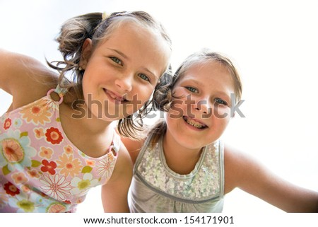 Portrait of two small happy  smiling children from bellow - stock photo