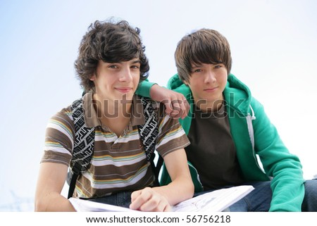 Portrait of two smiling boys with notebooks