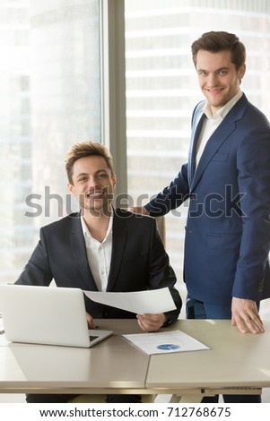 Portrait of two smiling businessmen working together with document in office and looking at camera. Satisfied boss standing near happy employee sitting at desk with laptop, positive colleagues concept