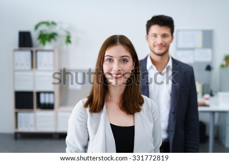 portrait of two smiling businesspeople looking at camera