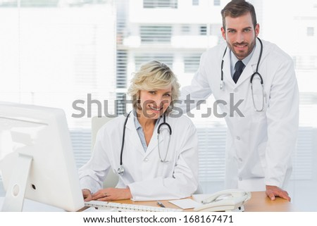 Portrait of two smiling doctors with computer at medical office