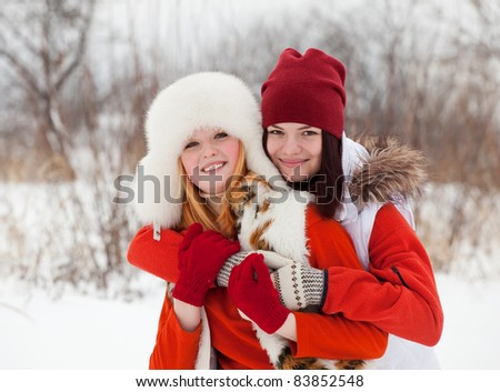 Portrait of  two smiling girls in winter - stock photo