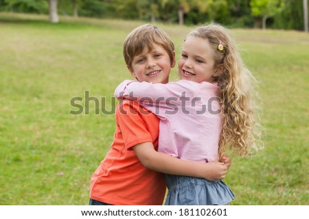 Portrait of two smiling kids hugging at the park - stock photo