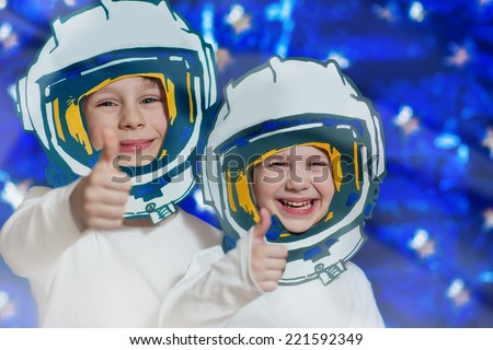 Portrait of two smiling kids in space suits. Cosmonautics Day concept. - stock photo