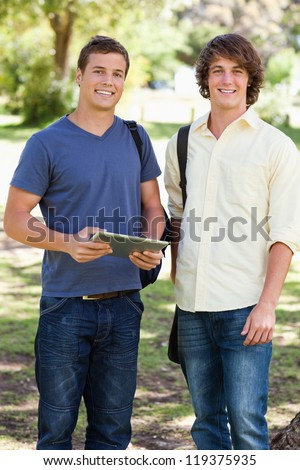 Portrait of two smiling male students with a touch pad in a park - stock photo