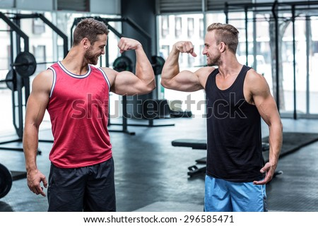Portrait of two smiling muscular men flexing biceps - stock photo