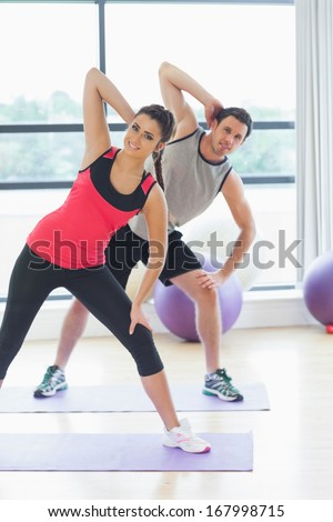 Portrait of two smiling people doing power fitness exercise at yoga class in fitness studio - stock photo