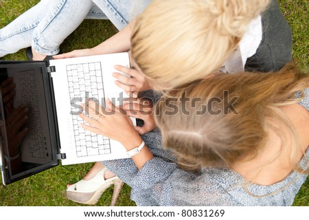 Portrait of two smiling women using laptop on a green meadow at the city park. Photo from above