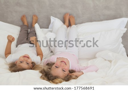 Portrait of two smiling young kids lying in bed at home - stock photo
