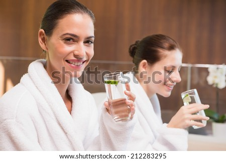 Portrait of two smiling young women in bathrobes drinking water - stock photo