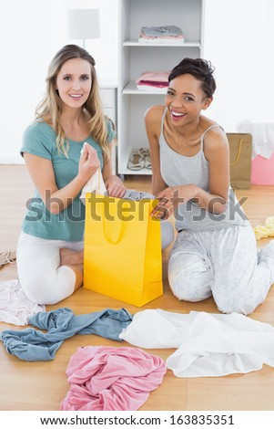 Portrait of two smiling young women sitting on the floor with shopping bag at home