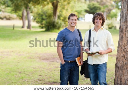 Portrait of two standing male students talking in a park