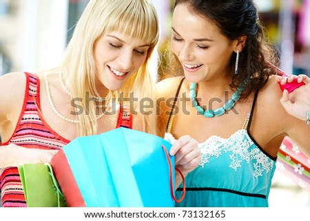 Portrait of two stylish women looking into paperbag with new clothes in shop - stock photo