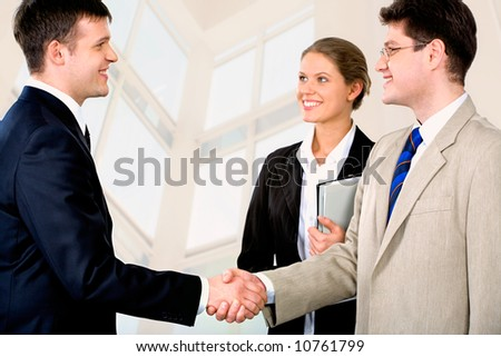 Portrait of two successful business partners shaking each other's hands with a smiling businesswoman standing near by and looking at them