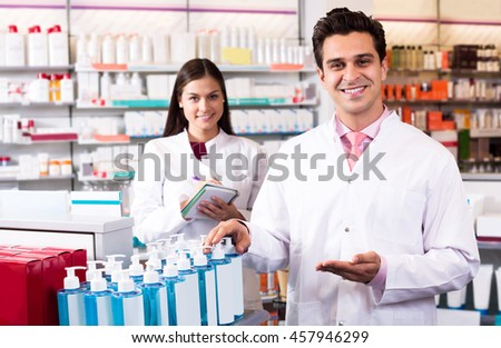 Portrait of two successful friendly pharmacists working in modern farmacy