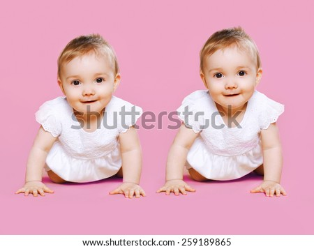 Portrait of two sweet twins baby crawls together - stock photo