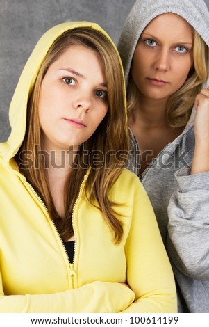 Portrait of two teen girls looking seriously into the camera. Studio shot against a gray background.